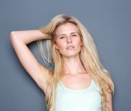 Sensual blond woman with hand in hair. Close up portrait of a sensual blond woman with hand in hair posing on gray background Stock Photo