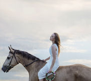 Sensual blond woman riding a brown stallion Stock Photos