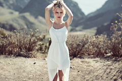 Sensual blond woman walking on the desert Stock Images