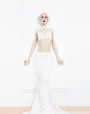 Sensual blond woman in white interior. Royalty Free Stock Photography