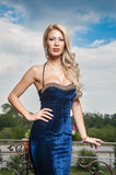Sensual blonde with blue dress on ledge Stock Images