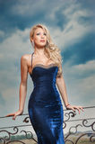 Sensual blonde with blue dress on ledge Royalty Free Stock Photo