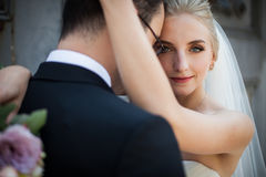 Sensual blonde bride hugging strong groom, face closeup Royalty Free Stock Photography