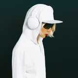 Sensual blonde DJ in sports white clothing. Listening to Music on black background. Urban fashion style Royalty Free Stock Image