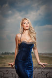 Sensual blonde with elegant blue dress posing on l Stock Photography