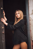 Sensual blonde girl in black shirt waiting near a door Stock Photography