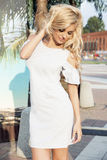 Sensual blonde girl posing. Sensual beautiful blonde woman with long curly hair posing outdoor wearing fashionable dress royalty free stock photography