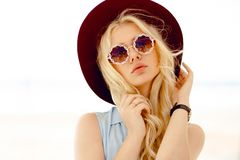 Sensual blonde girl with round floral sunglasses,curly hair,big lips and hat touches own hair and looking at camera. stock photos