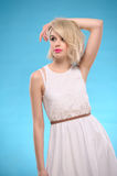 Sensual blonde hair woman. Sensual portrait of a beautiful blonde hair woman with white dress on blue background Stock Photography