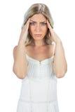 Sensual blonde having a headache. Sensual blonde on white background having a headache stock images