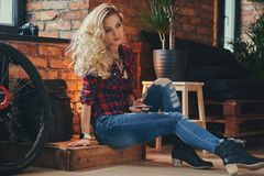 Sensual blonde hipster girl with long curly hair dressed in a fleece shirt and jeans holds a smartphone sitting on a. Wooden box at a studio with loft interior Royalty Free Stock Photos