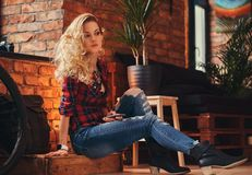 Sensual blonde hipster girl with long curly hair dressed in a fleece shirt and jeans holds a smartphone sitting on a. Wooden box at a studio with loft interior Stock Photos