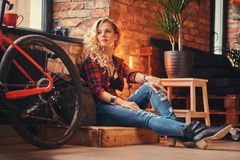 Sensual blonde hipster girl with long curly hair dressed in a fleece shirt and jeans sitting on a wooden box, looking Stock Photography