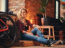 Sensual blonde hipster girl with long curly hair dressed in a fleece shirt and jeans sitting on a wooden box, looking Stock Image