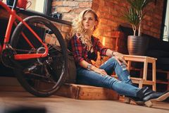 Sensual blonde hipster girl with long curly hair dressed in a fleece shirt and jeans sitting on a wooden box, looking Royalty Free Stock Images
