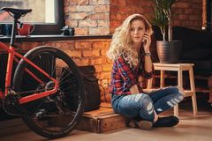 Sensual blonde hipster girl with long curly hair dressed in a fleece shirt and jeans holds a smartphone sitting on a Royalty Free Stock Photos