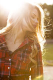 Sensual blonde model with long wavy hair in checkered dress posing in the park stock photos