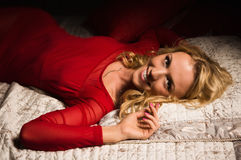 Sensual blonde in a red dress lying on the bed Royalty Free Stock Photos