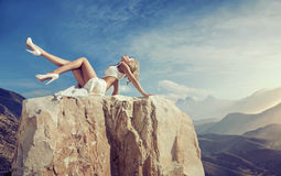 Sensual blonde relaxing on the rock Stock Images