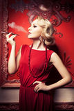 Sensual blonde smoking cigarette in red vintage room Stock Image
