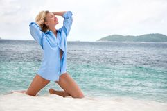 Sensual blonde woman on the beach in men's shirt Stock Image