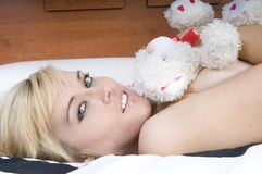 Sensual blonde woman on a bed Royalty Free Stock Photography