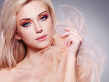 Sensual blonde woman covering by beige. Royalty Free Stock Images
