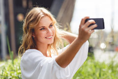Sensual blonde woman doing self-portrait in nature background Royalty Free Stock Photo