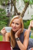 Sensual blonde woman lying in park on blanket. She is using red Royalty Free Stock Image