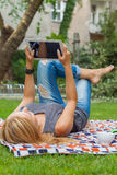 Sensual blonde woman lying in park on blanket. She is using whit Stock Photos