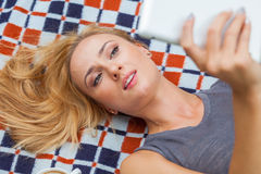 Sensual blonde woman lying in park on blanket. She is using whit Stock Photo