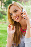 Sensual blonde woman in park using mobile phone. Outdoor photo. Stock Photography