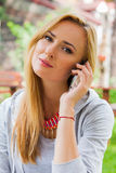 Sensual blonde woman in park using mobile phone. Outdoor photo. Stock Photos