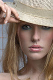 Sensual blonde woman peers out from under the brim. Of a hat royalty free stock image