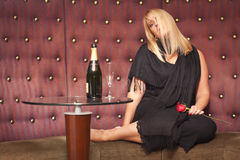 Sensual Blonde Woman Sitting Near Champagne and Rose Stock Photography