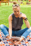 Sensual blonde woman sitting in park on blanket. She is using ta Stock Photos