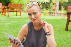 Sensual blonde woman sitting in park on blanket. She is using ta Royalty Free Stock Photography