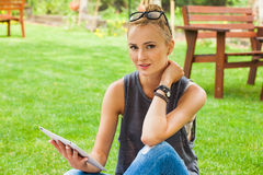 Sensual blonde woman sitting in park on blanket. She is using ta Royalty Free Stock Images