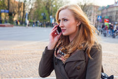 Sensual blonde woman using mobile phone. Outdoor photo,city back Stock Photo