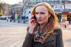 Sensual blonde woman using mobile phone. Outdoor photo,city back Royalty Free Stock Photos