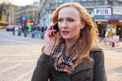 Sensual blonde woman using mobile phone. Outdoor photo,city back Royalty Free Stock Photography