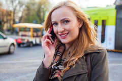 Sensual blonde woman using mobile phone. Outdoor photo,city back Royalty Free Stock Photo