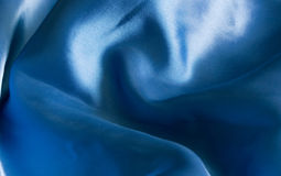 Sensual blue silk. Soft blue silk fabric backdrop with plenty of room for text Royalty Free Stock Photos