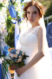 Sensual bride with dark hair in luxurious lace wedding dress with bouquet Royalty Free Stock Images