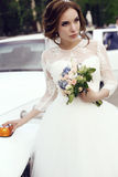 Sensual bride with dark hair in luxurious wedding dress posing beside car Royalty Free Stock Image