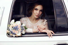 Sensual bride with dark hair in luxurious wedding dress posing in car Stock Photo