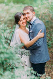 Sensual bride embracing with her loving groom. Close up wedding pair romantic moment in green summer park Stock Images