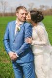 Sensual bride kissing happy groom to cheek. On nature Stock Photos