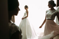 Sensual bride next to the window with her friends Royalty Free Stock Photos
