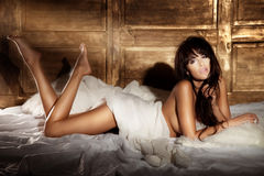 Sensual brunette beauty lying in white bed Royalty Free Stock Photo